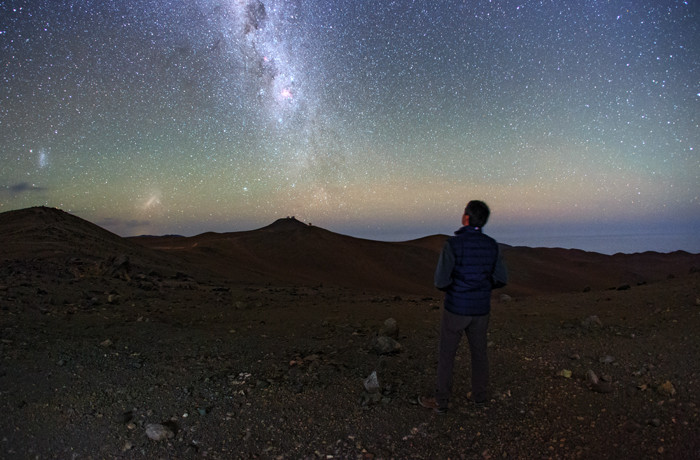 Young Man in Desert Landscape Looking up at Starry Sky and Milky Way