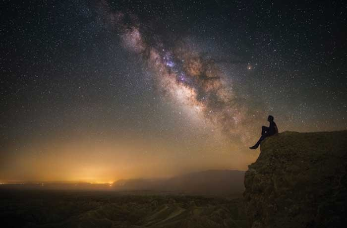 Young Man sitting on cliff gain up at the Milky Way in Borrego Springs California