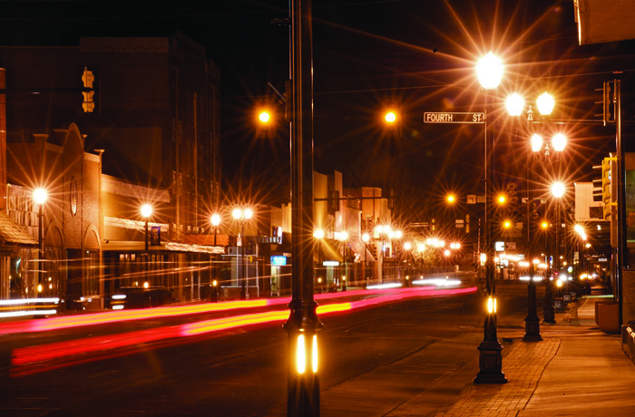 Downtown main street of Liberal, Kansas sports new streetlights with old-time character, but which pour light out in all directions and up into the sky.  With no shielding the exposed globes cause much glare that makes seeing difficult. Photo by Jim Richardson.