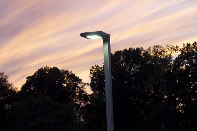 A shielded LED outdoor streetlight against a setting sky.