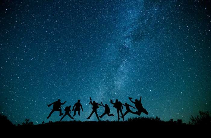 Group of Young People Jumping Up with Beautiful Starry Blue Sky in the Background