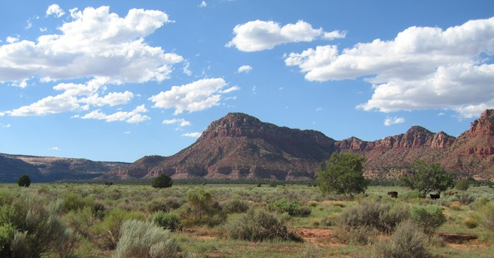 A daytime photo of Thunder Mountain Kaibab Paiute Indian Reservation with blue skies and white cloud above and a rolling landscape of green.