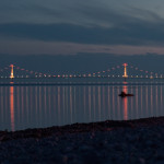 The Mackinac Bridge at twilight with colored lights that are reflecting in the water.