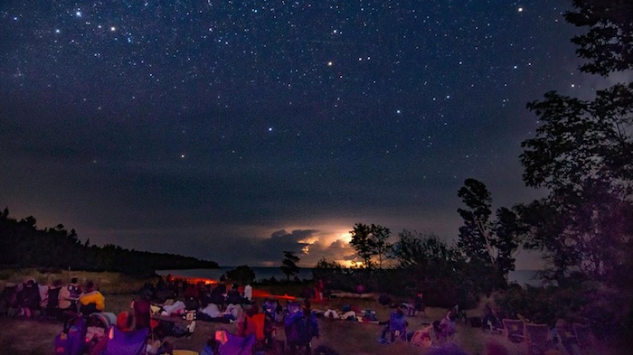 People sitting on the lawn lookin gup at a starry night sky at the Newport State Park during its Perseid meteor showers event.