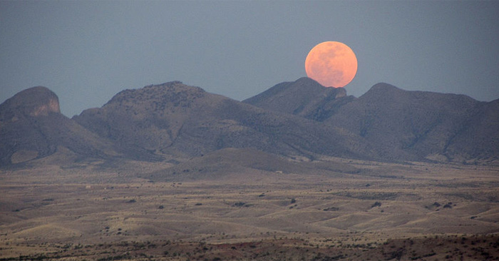 Full Supermoon rising over mountains