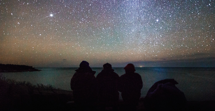 Two people huddled together looking out over Eagle Lake at Acadia National Park under a starry night sky.