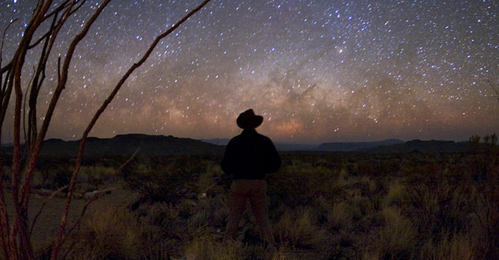 Man gazing up at the Milky Way at Big Bend National Park in Texas.