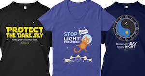 "The three IDA t-shirts side by side. One says ""Protect the Dark Side. Fight Light Pollution, You Must"" in yellow letter; Another says Stop Light pollution and has a cat in space and the other says ""Everyday needs a night"" and has a ying yang."