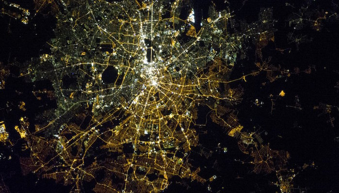 A satellite image of Berlin at night showing the difference between the lights of west and east Berlin.