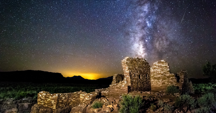 The Milky Way sets over Lomaki Puelbo at Wupatki National Monument, with the glow of Flagstaff in the distance. Photo by Flickr user CEBImagery, licensed under CC BY-NC 2.0.