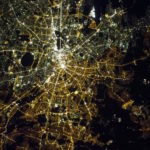 This photo shows the divide between East and West Berlin that is still visible at night from space. On the left are the gas lamps of the West and on the right, the orange high-pressure sodium lamps of the East, with a stark contrast between them. The image is a powerful reminder that lighting choices made by city planners are long lasting.