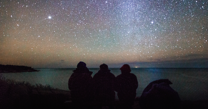Three people sit looking over the water at Acadia National Park. The night sky is filled with star and you can see a hint of he Milky Way.